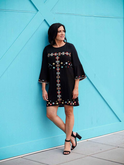 A woman models a black embroidered dress as an example of spring outfits for women.