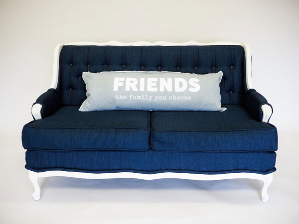 A blue couch decorated with a gray, linen pillow as an example of popular home decor trends in 2020.