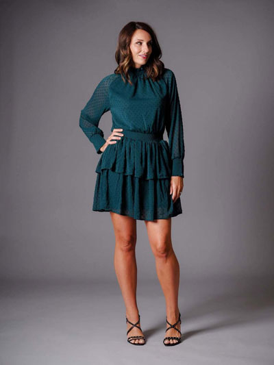A woman models an emerald green, casual boutique dress