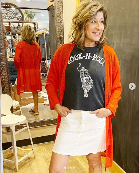 A woman models a cute Mother's Day outfit idea including a rock-n-roll graphic tee and mini skirt.