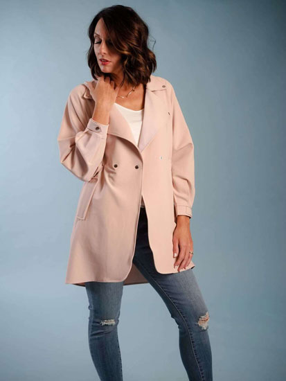 A woman models a cute Mother's Day outfit idea including a pale pink trench coat.