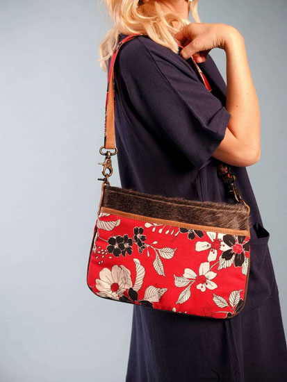 A woman models a cute Mother's Day outfit idea including a red, floral handbag.