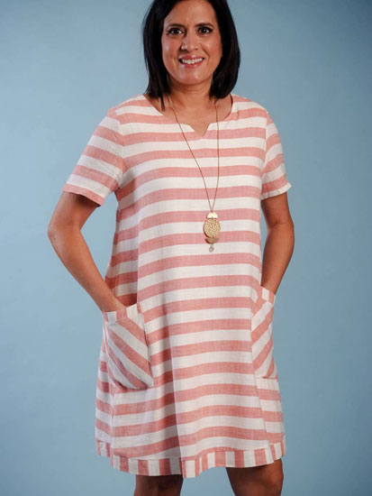 A woman models a cute Mother's Day outfit idea including a pink and white striped dress.