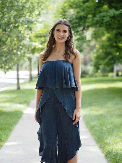 A woman models a strapless denim jumpsuit while standing in a grassy quad.