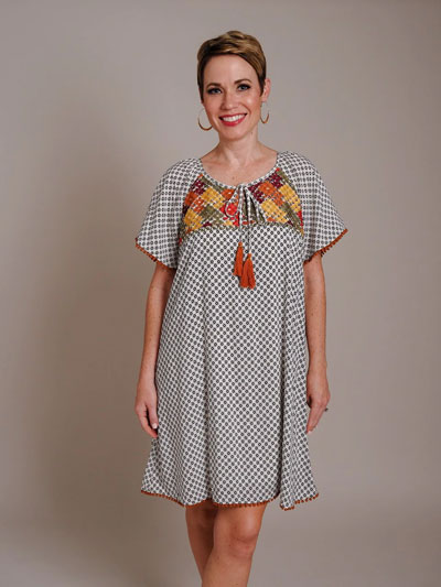 A woman models a bohemian embroidered casual boutique dress.