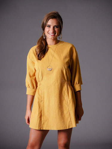 Woman models her autumn capsule wardrobe with a stylish yellow dress.