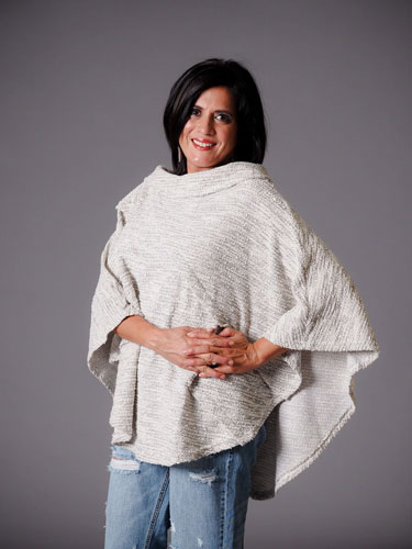 Woman flaunts her autumn capsule wardrobe with a stylish white poncho.