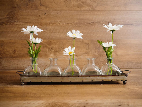 Dainty glass vases sit on a tray as an example of popular home decor trends in 2020.