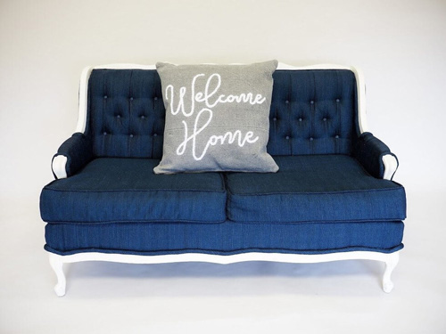 A gray pillow modeled on a couch as an example of rustic spring decor.