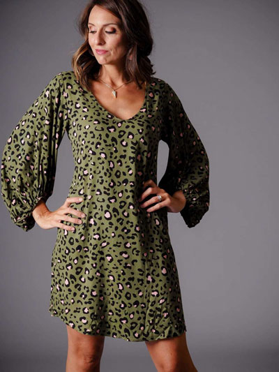 A woman models a green leopard print casual boutique dress