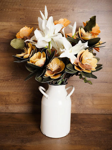 A rustic milk can filled with flowers as an example of farmhouse Easter decor.