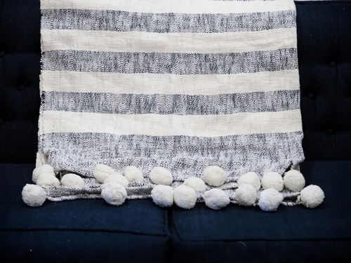 A white and gray striped pom-pom throw blanket modeled on a couch as an example of rustic spring decor.