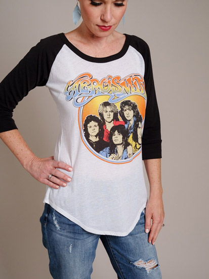 A woman models a baseball-styled rock-and-roll t-shirt as an example of spring outfits for women.