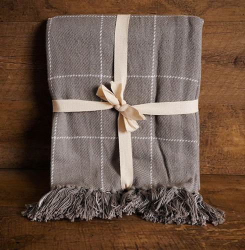A gray, plaid throw blanket sits against a wooden background as an example of rustic farmhouse Christmas decor.