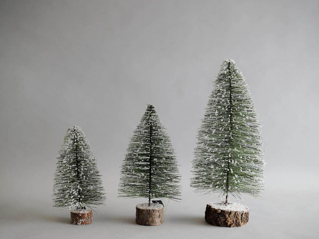 Three, faux snow-frosted Christmas tree rustic farmhouse Christmas decorations.
