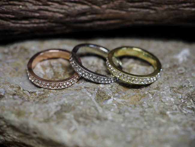 Three different colored rings sit on a stone surface.