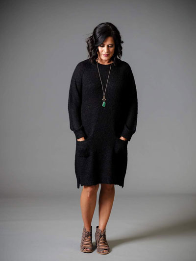 A woman models a casual black sweater boutique dress
