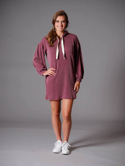 A woman models a pink, sweatshirt casual boutique dress