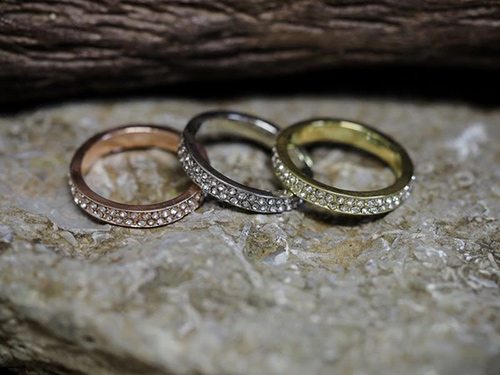 Three rings in gold, rose gold, and silver colors with glass stone embellishments.