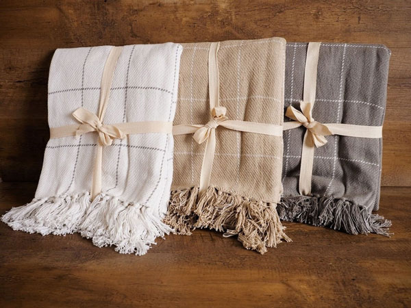 A collection of neutral throw blankets are stacked together as an example of popular home decor trends in 2020.