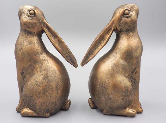 Two bronze rabbit rustic Easter decor centerpieces sit back back-to-back.