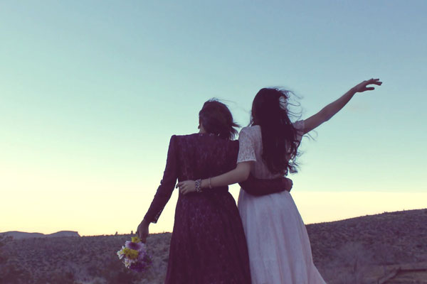 Two women wearing modern hippie style-clothes hold on to each other in the desert.