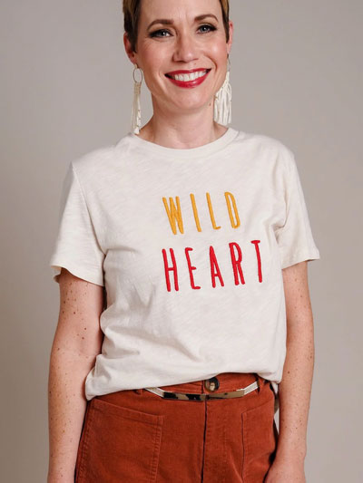 "Woman in white ""Wild Heart"" graphic t-shirt models how to how to wear graphic tees professionally."