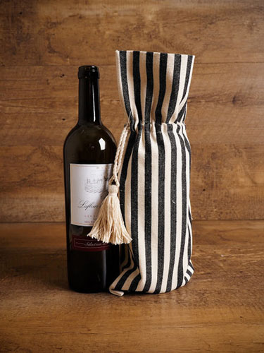 A bottle of wine next to a rustic, striped linen wine bag.