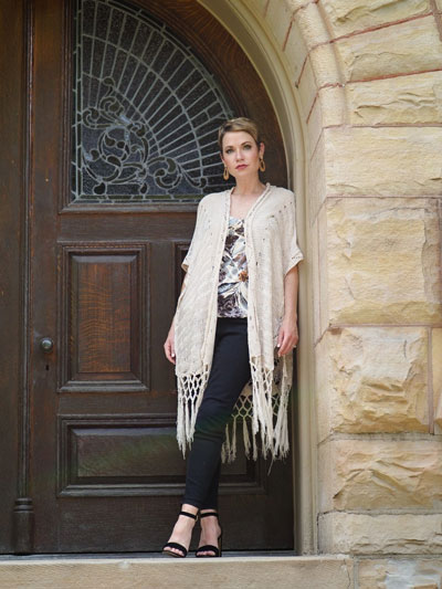 A woman stands in a stone doorway and models a graphic t-shirt under a white cardigan