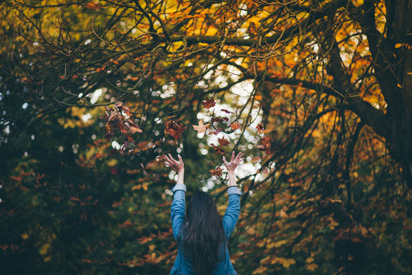 A woman throws up her hands as she stands in a forest full of autumn-colored trees.